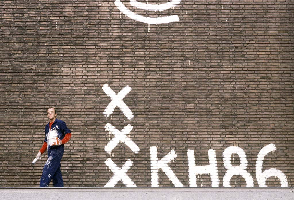 Keith_Haring_at-work-Amsterdam_muurschildering-depot-Stedelijk-1986-©-foto-Patricia-Steur