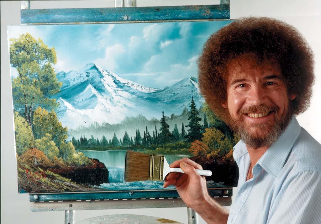 Bob_Ross staand bij de schildersezel_ bij publicatie vermelden credit © Bob Ross Inc.