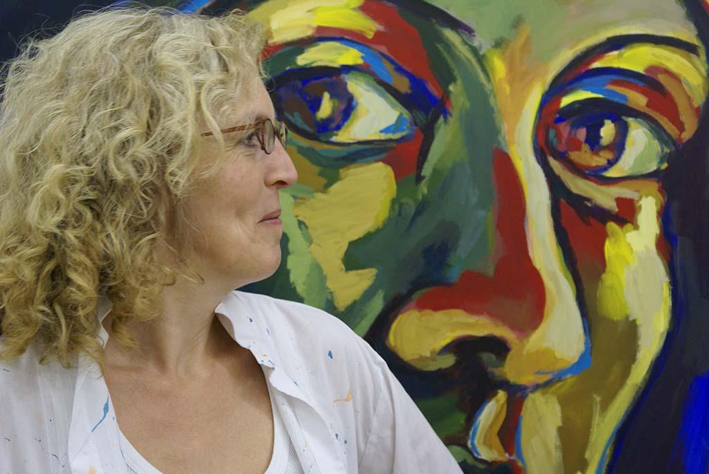 Elganan Jelsma in haar atelier, staand voor een portret ©Elganan Jelsma